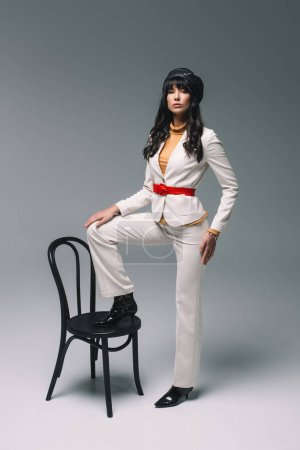 beautiful brunette woman in white suit putting leg on chair on gray