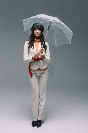 brunette woman in white suit standing with umbrella on gray
