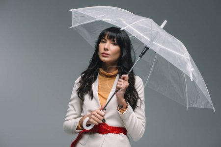 brunette woman in white jacket standing with umbrella isolated on gray