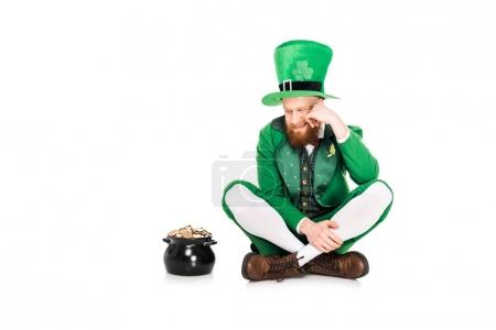 handsome leprechaun in green suit looking at pot of gold, isolated on white