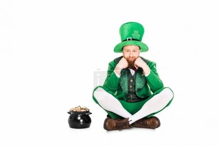 upset leprechaun in green suit sitting at pot of gold, isolated on white