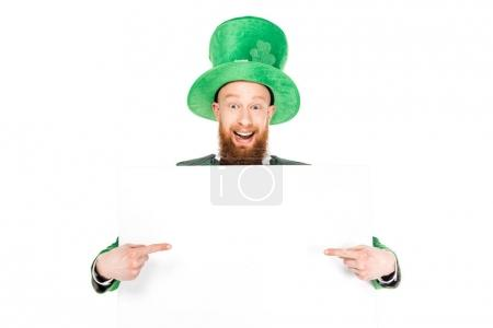 leprechaun in green suit pointing at blank placard, isolated on white