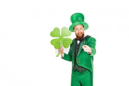 leprechaun in green suit pointing and holding clover, isolated on white