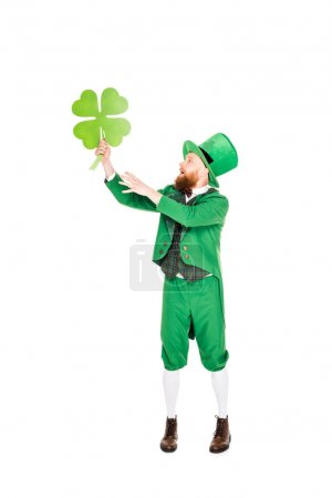 leprechaun in green suit and hat holding clover, isolated on white