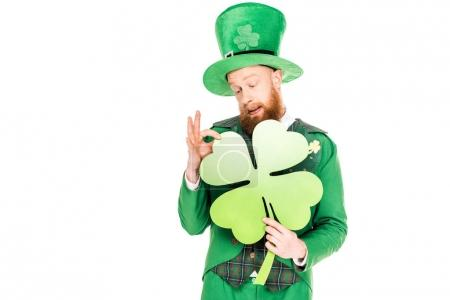 handsome leprechaun in green suit holding clover, isolated on white