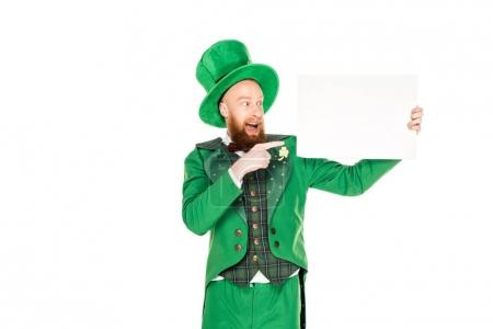 Photo pour Leprechaun en costume vert pointant vers la plaque blanche, isolé sur blanc - image libre de droit