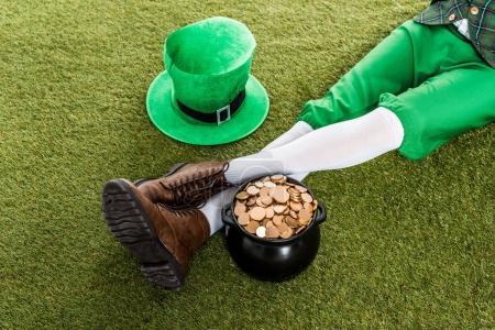 Photo pour Vue recadrée du lutin avec chapeau et pot d'or assis sur l'herbe verte - image libre de droit