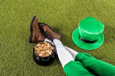 Photo pour Vue recadrée du lutin avec pot d'or et chapeau assis sur l'herbe verte - image libre de droit