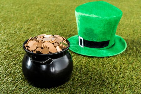 green hat and pot of gold on grass for st patricks day