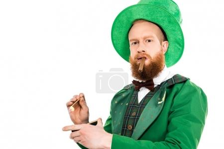 leprechaun in green costume and hat smoking cigar and looking at camera isolated on white