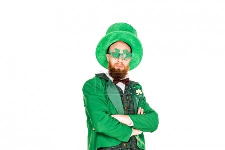 bearded man in green costume and clover shaped eyeglasses standing with crossed arms isolated on white, st patricks day concept