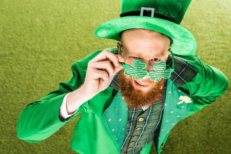 high angle view of bearded man in green costume wearing clover shaped eyeglasses and looking at camera, st patricks day concept