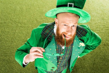 high angle view of bearded man in green costume holding clover shaped eyeglasses and looking at camera, st patricks day concept
