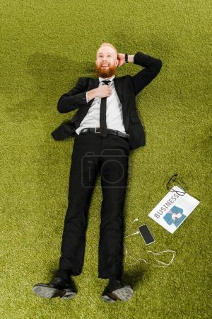 high angle view of smiling young businessman lying on green grass with smartphone, earphones, eyeglasses and newspaper