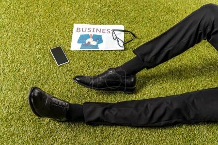 partial view of male legs in stylish leather shoes, eyeglasses, newspaper and smartphone with blank screen on green grass