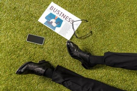 cropped shot of male legs in stylish leather shoes, eyeglasses, newspaper and smartphone with blank screen on green grass