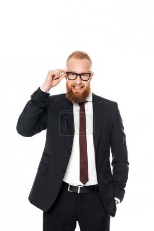 handsome young businessman adjusting eyeglasses and smiling at camera isolated on white