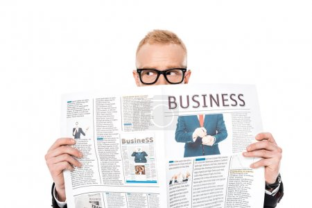young man in eyeglasses hiding behind business newspaper isolated on white