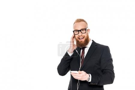 smiling bearded businessman in earphones listening music with smartphone isolated on white