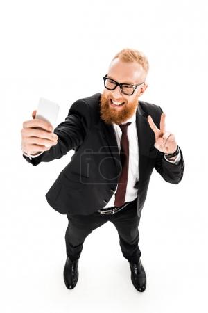 high angle view of smiling bearded businessman taking selfie with smartphone isolated on white