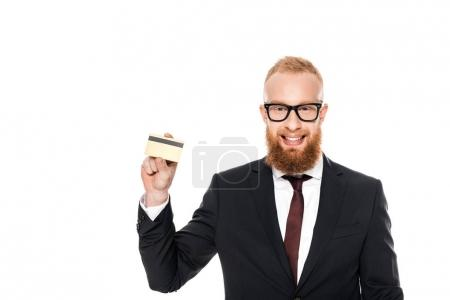 young bearded businessman in eyeglasses holding credit card and smiling at camera isolated on white