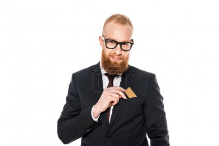 smiling bearded businessman putting credit card in pocket of suit jacket isolated on white