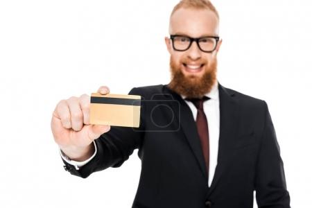 close-up view of handsome bearded businessman in eyeglasses holding credit card and smiling at camera isolated on white