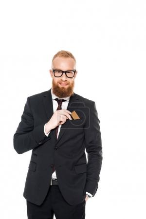 handsome bearded businessman in eyeglasses holding credit card and smiling at camera isolated on white