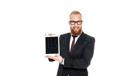 handsome bearded businessman holding digital tablet with blank screen and smiling at camera isolated on white