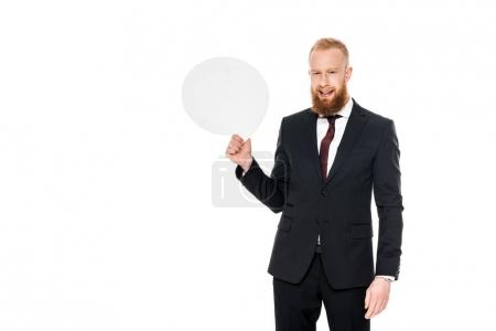 handsome bearded businessman holding blank speech bubble and smiling at camera isolated on white