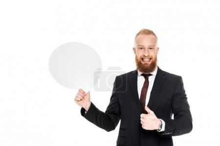 smiling bearded businessman holding blank speech bubble and showing thumb up isolated on white
