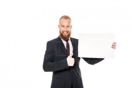 Photo for Bearded yung businessman holding blank banner and showing thumb up isolated on white - Royalty Free Image