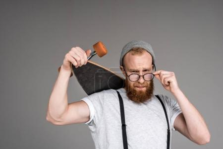 handsome bearded man in spectacles holding longboard and looking at camera on grey