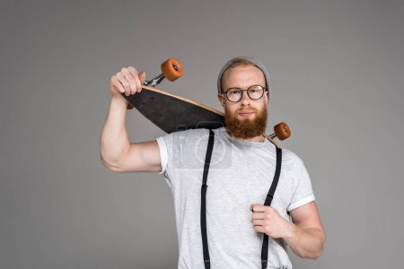 handsome bearded man holding longboard on shoulders and looking at camera on grey