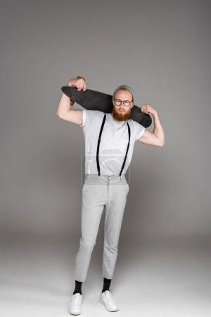 handsome stylish bearded man holding longboard on shoulders and looking at camera on grey