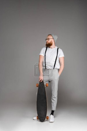 handsome stylish bearded man standing with skateboard and looking away on grey