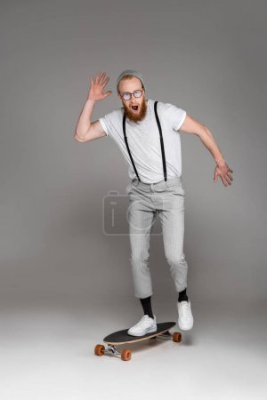 scared bearded man with open mouth standing on longboard and looking at camera on grey