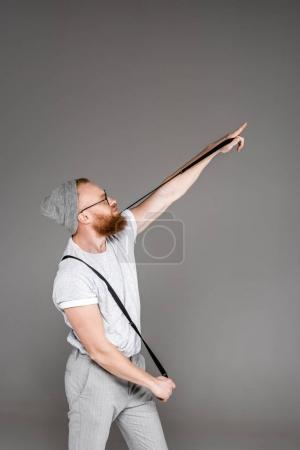 stylish bearded man holding suspenders and pointing away isolated on grey