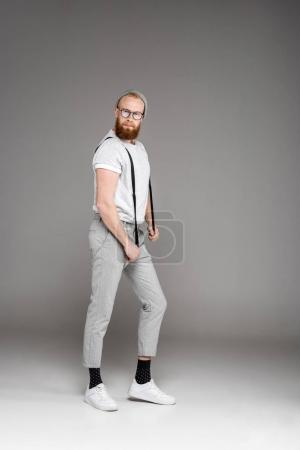 fashionable bearded man in spectacles holding suspenders and looking at camera on grey