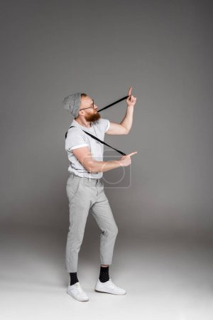 stylish bearded man playing with suspenders and pointing with fingers on grey