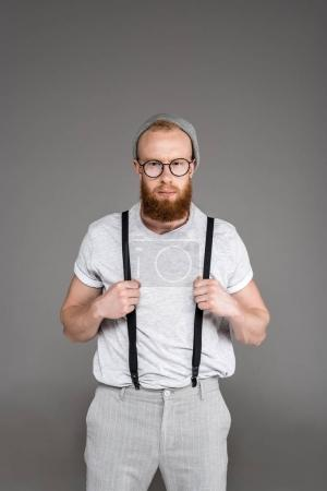 portrait of handsome stylish bearded man in suspenders looking at camera isolated on grey