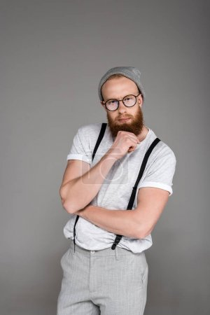 portrait of stylish bearded man in suspenders looking at camera isolated on grey