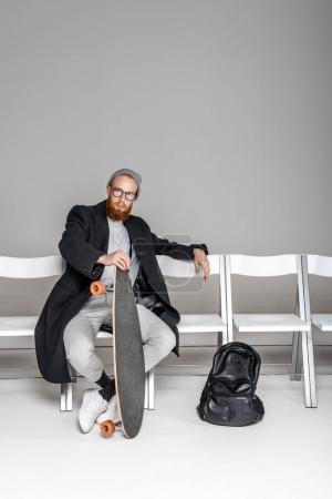 stylish man in overcoat and spectacles holding skateboard while sitting on chair on grey