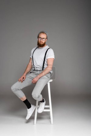 Photo for Stylish bearded hipster in eyeglasees sitting on stool and looking at camera on grey - Royalty Free Image