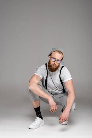 stylish bearded man in hat and eyeglasses crouching and looking at camera on grey