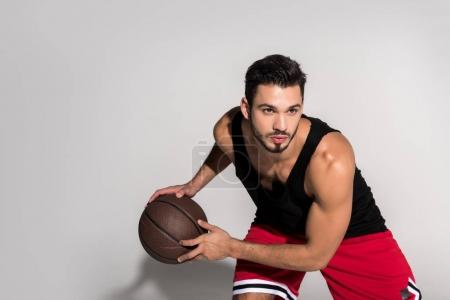 focused young athletic man playing basketball on white