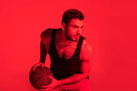 focused young sportsman playing basketball at contrast red light