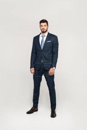 Foto de Vista de la longitud total de elegante guapo joven hombre de negocios mirando a cámara aislada en gris - Imagen libre de derechos