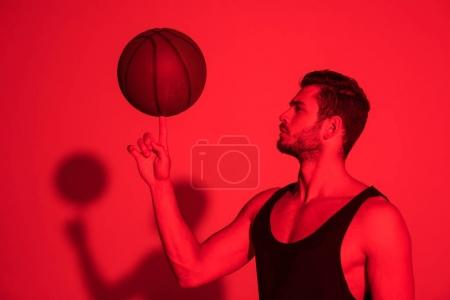 muscular sportsman holding basketball ball on finger at contrast red light