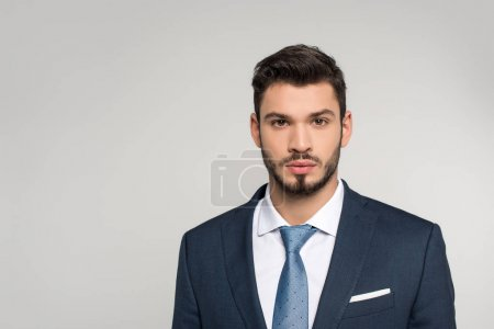 portrait of handsome young businessman looking at camera isolated on grey